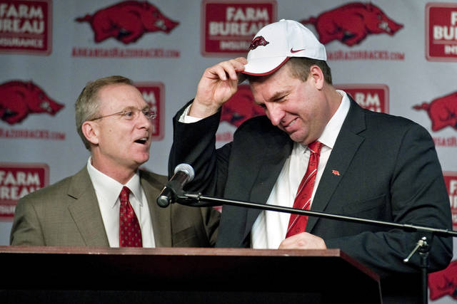 Arkansas athletic director Jeff Long, left, presents Bret Bielema with a cap as Bielema is introduced as the school's new head coach during an NCAA college football news conference in Fayetteville, Ark., Wednesday, Dec. 5, 2012. Bielema, who will be paid $3.2 million annually for six years, replaces interim coach John L. Smith, who was hired after Bobby Petrino was fired in April. (AP Photo/April L. Brown)