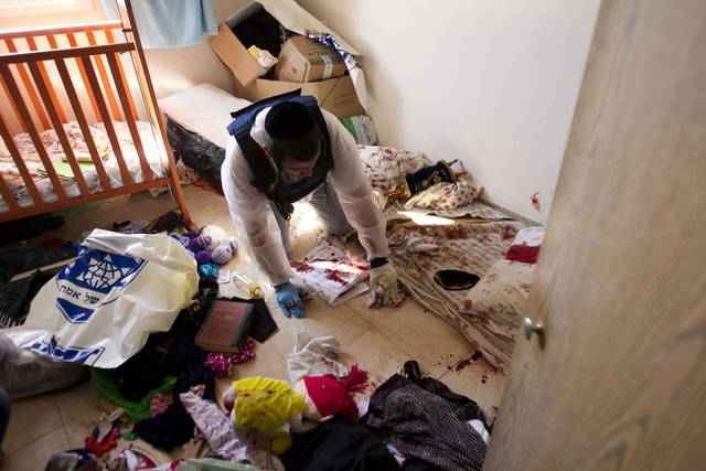 A Zaka volunteers clean blood stains from a children's room in an apartment in a building that was hit by a rocket fired from the Gaza Strip, where three people were killed in Kiryat Malachi, southern Israel, Kiryat Malachi, southern Israel,Thursday, Nov. 15, 2012. Militants in the Hamas-ruled Gaza Strip killed three Israelis on Thursday in a rocket attack liable to deepen a bruising Israeli air, naval and artillery offensive against Palestinian rocket squads. The casualties were the first in Israel since it launched its operation on Wednesday with the assassination of Hamas� top military commander. (AP Photo/Ariel Schalit)