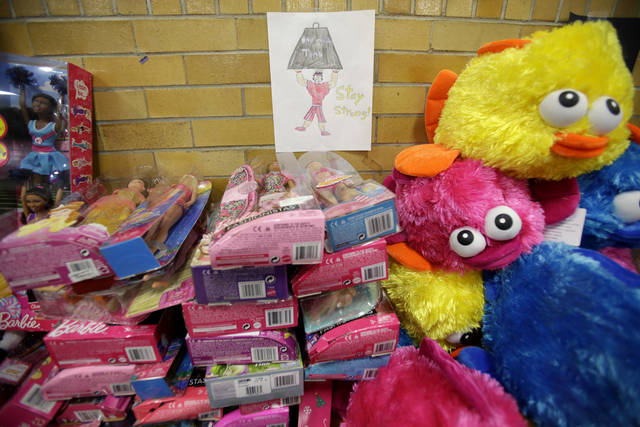 A message of support hangs over a table full of donated toys at the town hall in Newtown, Conn., Friday, Dec. 21, 2012.   (AP Photo/Seth Wenig) ORG XMIT: CTSW125