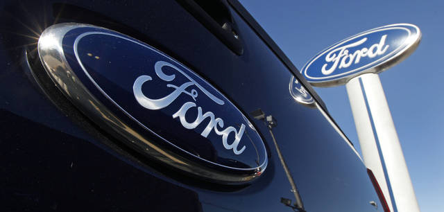 FILE - This Oct. 25, 2011 file photo shows a Ford logo on the tailgate of a pick-up truck, and on a Ford dealership sign at Salem Ford in Salem, N.H. Moody's Investors Service on Tuesday, May 22, 2012 raised Ford's debt ratings to investment-grade for the first time in seven years. The upgrade means that all Ford's assets, including factories and the blue oval logo, are back in the company's hands and will no longer be used to secure the company's debt. Ford posted the assets as collateral in 2006 in order to get a $23.5 billion loan and avoid bankruptcy. (AP Photo/Charles Krupa, File)