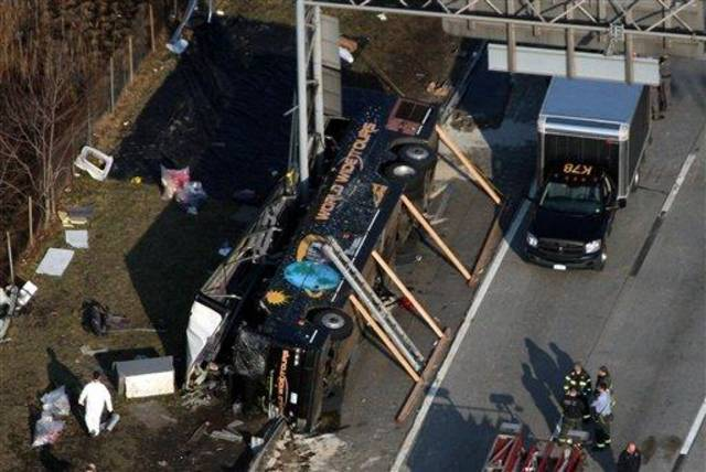 Emergency personnel respond to the bus crash on Interstate 95 in the Bronx borough of New York, Saturday, March 12, 2011. At least 14 people died when the bus, returning to New York from a casino in Connecticut, flipped onto its side and was sliced in half by the support pole for a large sign.(AP Photo/The Journal News, Frank Becerra Jr.)