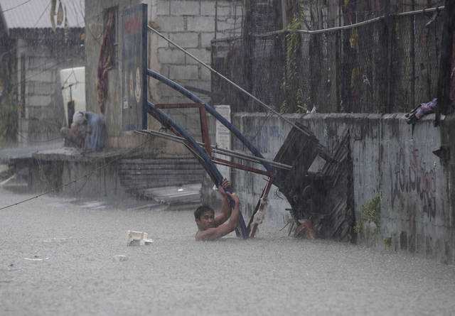 A man clings on to the pole of a basketball court as he tries to cross flooded area in Quezon City, north of Manila, Philippines, on Tuesday Aug. 7, 2012. Relentless rains submerged half of the sprawling Philippine capital, triggered a landslide that killed several people and sent emergency crews scrambling Tuesday to rescue and evacuate tens of thousands of residents. (AP Photo/Aaron Favila)