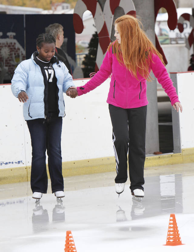 Sasha Logoutine helps 11-year-old Uzima Mangrum get started on the ice, as an outdoor skating rink opens at Edmond's Festival Market Place in Edmond, OK, Friday, Nov. 25, 2011. By Paul Hellstern, The Oklahoman