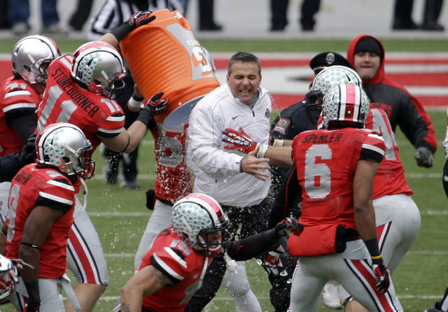 Ohio State head coach Urban Meyer, center, gets doused by senior wide receiver Jake Stoneburner (11) after their 26-21 win over Michigan in an NCAA college football game Saturday, Nov. 24, 2012, in Columbus, Ohio. (AP Photo/Mark Duncan)