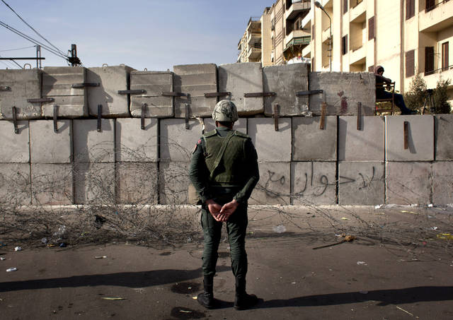 An Egyptian soldier stands guard in front of the presidential palace in Cairo, Egypt, Sunday, Dec. 9, 2012. Egypt's liberal opposition has called for more protests on Sunday after the president made concessions overnight that fell short of their demands to rescind a draft constitution going to a referendum on Dec. 15. (AP Photo/Nasser Nasser)