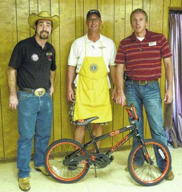 Michael Eliis presents a bike made on stage by Aaron Tippin to Lions Club Spaghetti Dinner Chair Daylin Hash and Lions Toy Box Chair Brian Bond for the Toy Box.