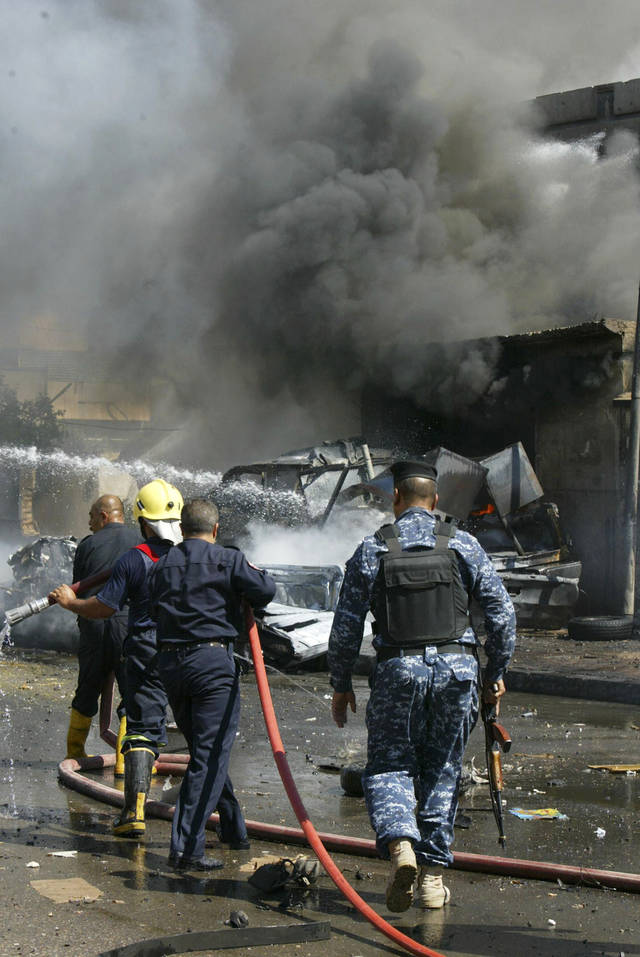 Iraqi firefighters extinguish flames after a car bomb attack in Kirkuk, 290 kilometers (180 miles) north of Baghdad, Iraq, Thursday, Sept. 29, 2011. A suicide bomber detonated his explosives packed car near a bank where policemen were picking up their paychecks, killing and wounding scores of people, police said. (AP Photo/Emad Matti)