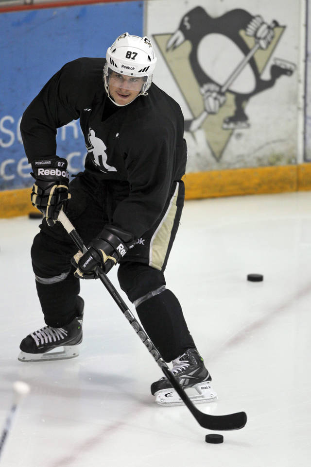 Pittsburgh Penguins captain Sidney Crosby, wearing a sweater with a National Hockey Players' Association logo on it, skates past a Penguins hockey team logo as he takes part in an informal workout at the Iceoplex in Canonsburg, Pa., on Thursday, Oct. 11, 2012, a day that the NHL would've opened the regular season if it weren't for the current lockout. (AP Photo/Keith Srakocic)