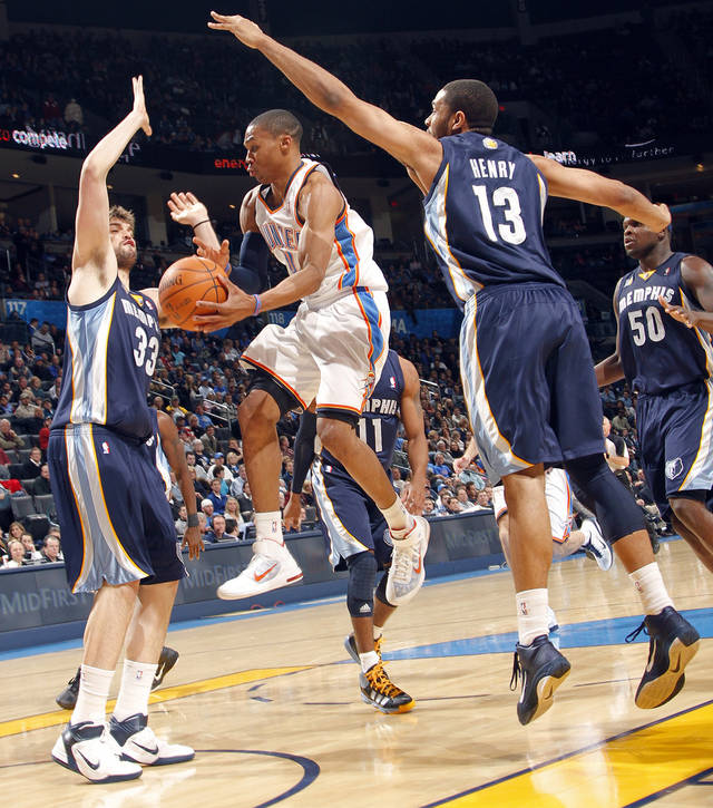 The Thunder's Russell Westbrook (0) drives the ball between Memphis' Marc Gasol (33) and Xavier Henry (13) during the NBA basketball game between the Oklahoma City Thunder and the Memphis Grizzlies at the Oklahoma City Arena on Tuesday, Feb. 8, 2011, Oklahoma City, Okla.  Photo by Chris Landsberger, The Oklahoman