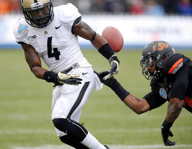 Oklahoma State's Justin Gilbert (4) knocks the ball away from Purdue's Taylor Richards (4) during the Heart of Dallas Bowl football game between Oklahoma State University and Purdue University at the Cotton Bowl in Dallas, Tuesday, Jan. 1, 2013. Oklahoma State won 58-14. Photo by Bryan Terry, The Oklahoman