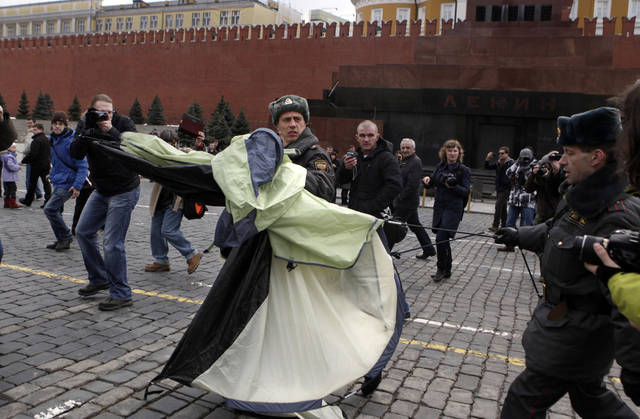 A police officer carries a tent which was set up by opposition leader Yevgeniya Chirikova, unseen, during a protest at the Red Square in Moscow, Sunday, April 8, 2012. Police arrested prominent opposition leader along with several other activists when they tried to put up a small tent on the Red Square. Opposition activists called for supporters to walk around Red Square on Sunday wearing the white ribbons that have become a symbol of the protest movement against Prime Minister Vladimir Putin. Putin will begin serving a third presidential term in May. (AP Photo/Maria Turchenkova)