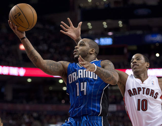 Orlando Magic guard Jameer Nelson (14) drives to the hoop past Toronto Raptors guard DeMar DeRozan (10) during first half NBA action in Toronto on Friday Dec. 21, 2012. (AP Photo/The Canadian Press, Frank Gunn)