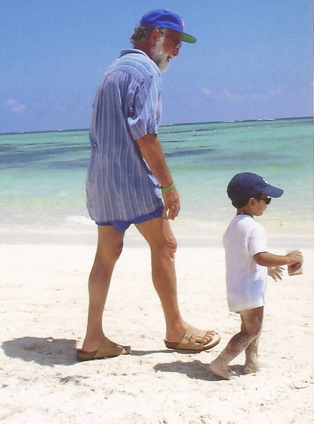 This undated photo provided by Jeff Spiegel shows his father, Robert Spiegel, walking with his grandson on a beach. Robert Spiegel died Wednesday, Nov. 30, 2011, and was eulogized in a quirky obituary written by his son Jeff that appeared Friday, Dec. 2, 2011 in central Connecticut newspapers. (AP Photo/Jeff Spiegel)