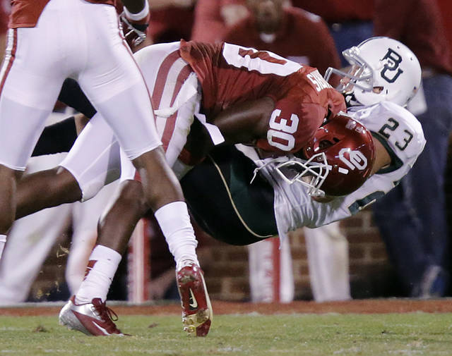 Oklahoma's Javon Harris (30) brings down Baylor's Clay Fuller (23) during the college football game between the University of Oklahoma Sooners (OU) and Baylor University Bears (BU) at Gaylord Family - Oklahoma Memorial Stadium on Saturday, Nov. 10, 2012, in Norman, Okla.  Photo by Chris Landsberger, The Oklahoman