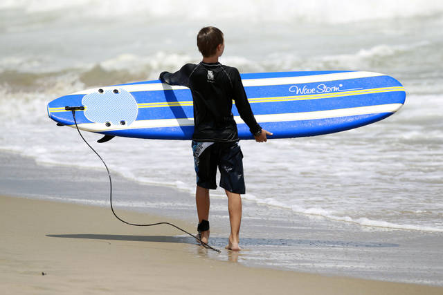 <p>A young surfer carries his surfboard as he looks out at the Atlantic Ocean in Manasquan, N.J., Monday, July, 16, 2012. (AP Photo/Mel Evans)</p>