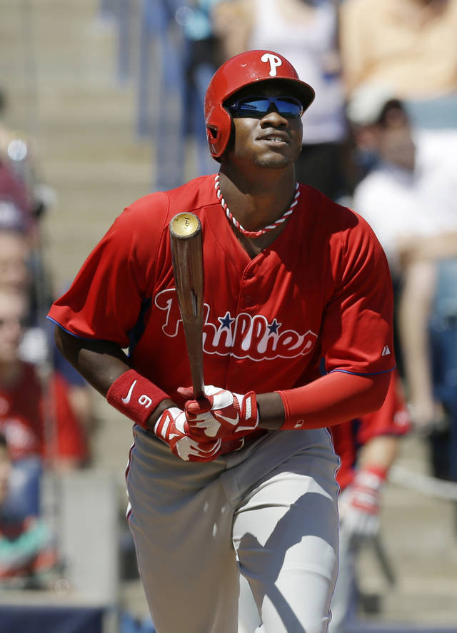 Philadelphia Phillies Domonic Brown watches his 3-run home run off New York Yankees starting pitcher Hiroki Kuroda during the fourth inning of a spring training baseball game at Steinbrenner Field in Tampa, Fla., Saturday, March 16, 2013.  (AP Photo/Kathy Willens)