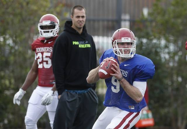 Former OU quarterback Landry Jones, center, watches as Trevor Knight throws during a spring practice in March. Knight is battling to replace Jones. AP Photo