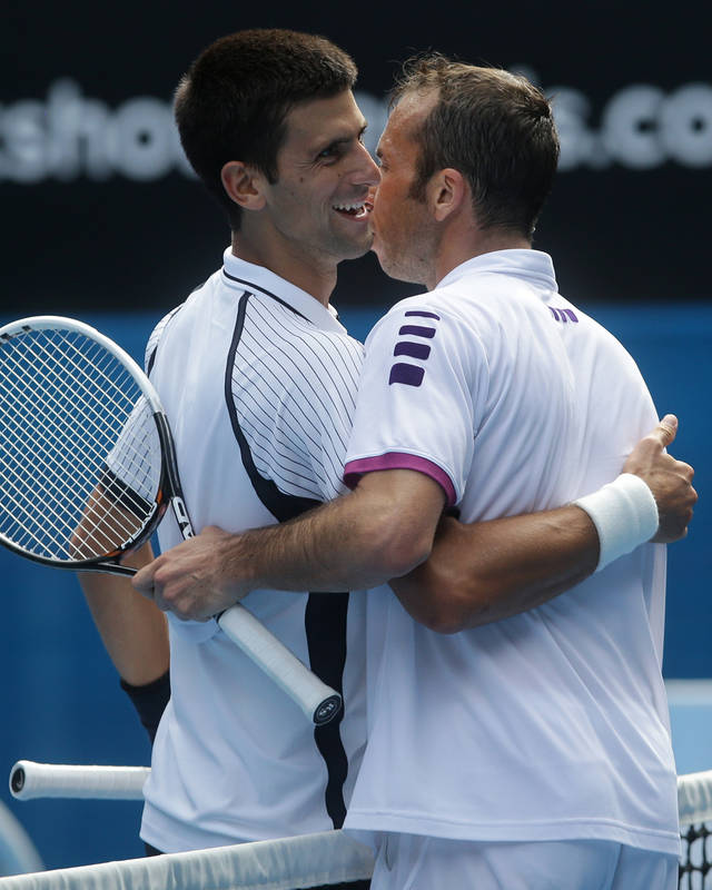 Serbia's Novak Djokovic, left, is embraced by Radek Stepanek of the Czech Republic following their third round match at the Australian Open tennis championship in Melbourne, Australia, Friday, Jan. 18, 2013. (AP Photo/Dita Alangkara)