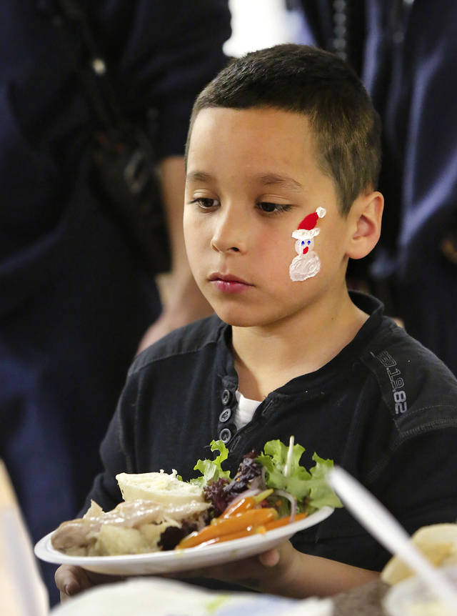 Nathan, a second-grade student, carries a full plate of food to his table.