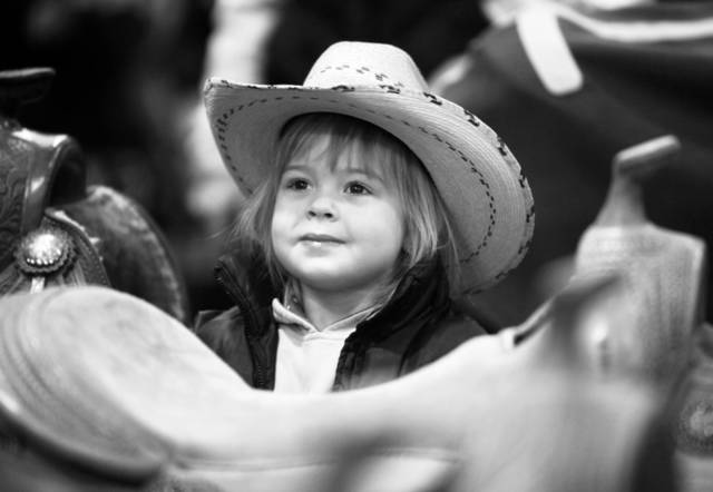 Eva Smallegan, 3, of Michigan, waits while her parents look at saddles during the National Reining Horse Association show Saturday at State Fair Park in Oklahoma City. PHOTOS BY PAUL HELLSTERN, THE OKLAHOMAN