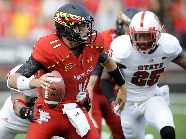 Maryland quarterback Perry Hills (11) looks to pass against North Carolina State safety Dontae Johnson (25) and linebacker Brandon Pittman, back left, during the first half of an NCAA football game, Saturday, Oct. 20, 2012, in College Park, Md. (AP Photo/Nick Wass)
