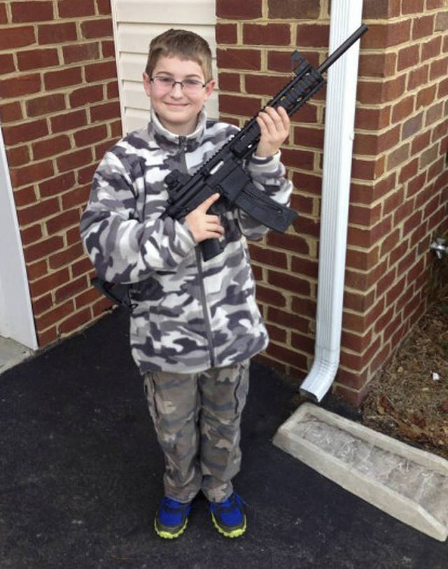 CORRECTS BOY'S AGE TO 10 - This undated photo provided by Shawn Moore shows his son Josh, 10, holding a rifle his father gave him for his 11th birthday, at their home in Carneys Point, N.J.  The Moore family claims this photo, posted on Facebook, led the state's child welfare agency to the family's house, Friday, March 15, 2013, demanding to be let inside to inspect their guns. (AP Photo/Shawn Moore)