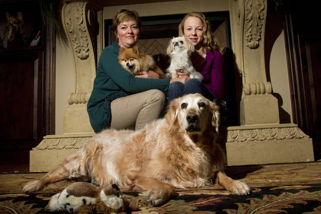 In this Saturday, Dec. 10, 2011 photo, Serena Brant, left, holds Max while her daughter Melissa, 12, holds Mia as they sit by Ali, foreground, their 10-year-old golden retriever at their home in Littleton, Colo. The Brants have spent over $8,000 on medicine alone to help care for Ali since they got her 10 years ago as a puppy from a pet store in a local mall near their home. (AP Photo/Barry Gutierrez)