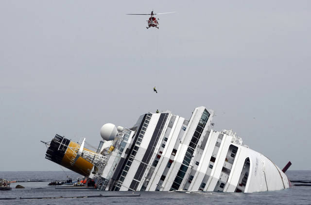 FILE - This Jan. 31, 2012 file photo shows an Italian firefighter being lowered from a helicopter onto the grounded cruise ship Costa Concordia off the Tuscan island of Giglio, Italy. Court-appointed experts have pointed the finger of blame primarily at the captain of a cruise ship that ran aground off Italy, but also faulted the crew and ship owner for a series of blunders, delays and security breaches that contributed to the disaster and the deaths of 32 people. (AP Photo/Pier Paolo Cito, file)