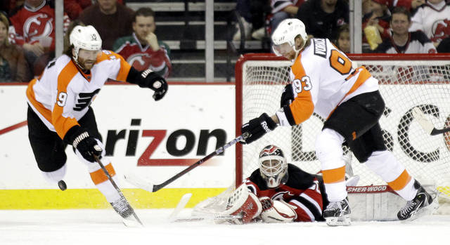 New Jersey Devils goalie Martin Brodeur, bottom, deflects a shot as Philadelphia Flyers' Scott Hartnell (19) and Jakub Voracek, of the Czech Republic, reach for the puck during the second period of Game 3 of a second-round NHL hockey Stanley Cup playoff series, Thursday, May 3, 2012, in Newark, N.J. (AP Photo/Julio Cortez)
