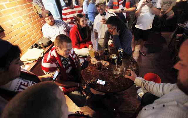 Members of the American Outlaws crowd around a couple of cell phones capable of streaming the match after satellite TV was interrupted by inclement weather at Skinny Slim's Public House in Bricktown on July 16, 2013. Photo by K.T. King