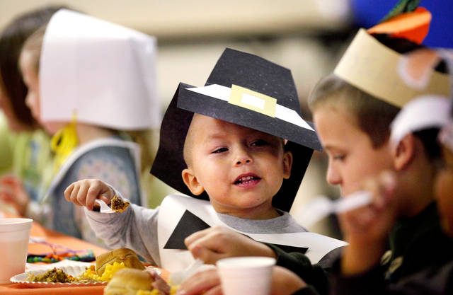 In this photo taken Nov. 21, 2011, Alex Vasquez, a pre-kindergarten student at Cleveland Bailey Elementary School in Midwest City, Okla., talks to a fourth grader while participating in the annual Thanksgiving meal in the school cafeteria. Teacher Linda Curry has been organizing the event at the school for 18 years. She said the dinner allows her students to her students learn about the history and meaning of Thanksgiving by dressing as Pilgrims and Indians and enjoying a traditional Thanksgiving meal. (AP Photo/The Oklahoman, Jim Beckel)  ORG XMIT: OKOKL102