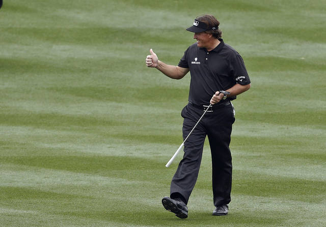 Phil Mickelson gives a thumbs-up to the cheering crowd as he walks up the 18th fairway during the final round of the Waste Management Phoenix Open golf tournament on Sunday, Feb. 3, 2013, in Scottsdale, Ariz. (AP Photo/Ross D. Franklin)