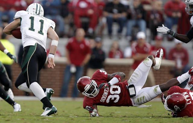 Baylor's Nick Florence (11) runs by Oklahoma's Javon Harris (30) during the college football game between the University of Oklahoma Sooners (OU) and Baylor University Bears (BU) at Gaylord Family - Oklahoma Memorial Stadium on Saturday, Nov. 10, 2012, in Norman, Okla.  Photo by Chris Landsberger, The Oklahoman