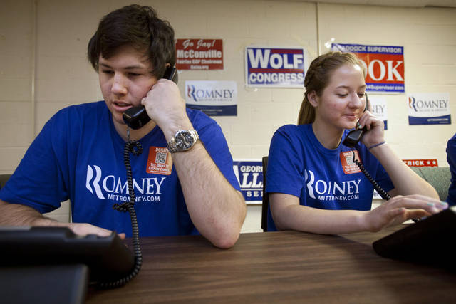 Bryan Munks, 19, of Arlington, Va., left, and Priscilla Houk, 17, of Fairfax, Va., make calls for the Romney campaign while wearing quick response code stickers, known as QR codes, in Fairfax, Va., on Tuesday, June 19, 2012. The presidential ground game has gone high tech, marrying old-school organizing work with innovative digital tools. The T-shirts that Romney campaign volunteers wear in Virginia feature a digital code that voters can zap with their smart phones to learn more about the Republican presidential hopeful, which gives Romney field organizers valuable information on how to reach them in the future. (AP Photo/Jacquelyn Martin)