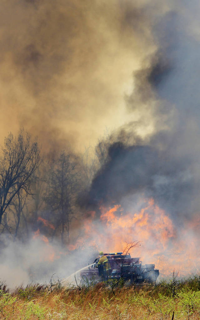 A firefighter on a brush pumper moves into a field at NE 73 Street and Post Road to deal with a grass fire fueled by dead tree limbs from previous ice storms in Oklahoma City Wednesday, April 6, 2011.  Photo by Paul B. Southerlan, The Oklahoman