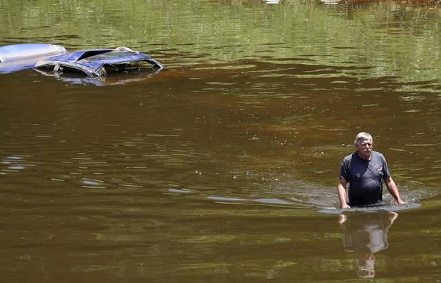 CAR RECOVERY / RECOVER / FLASH FLOODS / TORRENTIAL RAIN / FLOOD / FLOODING / AFTERMATH: Robert Channler of Car Cab Wrecker Service wades through the river after checking the vehicals VIN number. Cars were found in the Oklahoma River on Thursday June 17th, 2010. Photo by Mitchell Alcala.  ORG XMIT: KOD