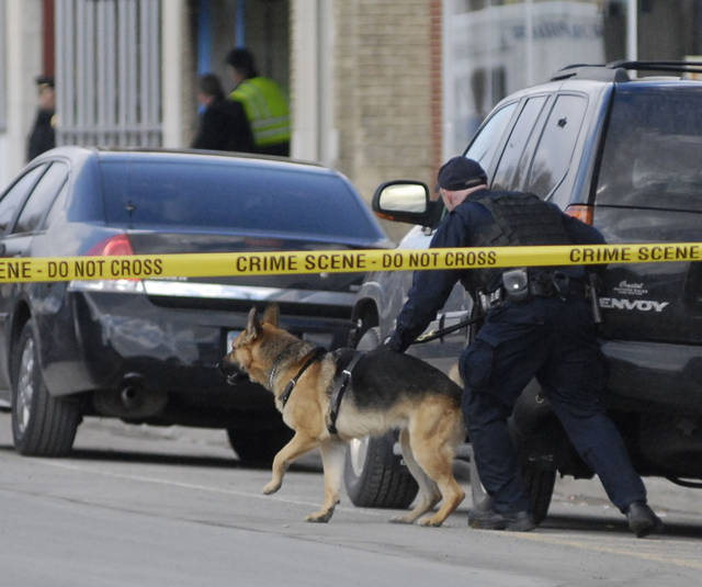 In this March 13, 2013 photo, a police officer with a dog ducks for cover as gunshots were heard not far from where accused gunman Kurt Myers had holed up in an abandoned bar in the village of Herkimer, N.Y., after a shooting rampage that left four dead.  Police and Myers, 64, of neighboring Mohawk, were in a standoff until Thursday monring when  Myers opened fire through a door at officers, killing an FBI dog. Police returned fire, killing Myers, State police Superintendent Joseph D'Amico said.  (AP Photo/Observer-Dispatch, Rob Roth)