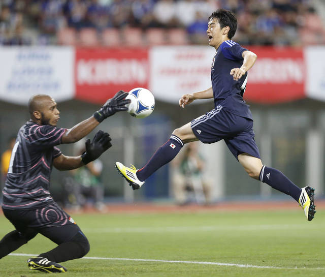 Japan's Shinji Kagawa, right, leaps near UAE's goal keeper Ali Khasif as he attempts to score a goal during a friendly soccer match in Niigata, Japan, Thursday, Sept. 6, 2012. (AP Photo/Kyodo News) JAPAN OUT, MANDATORY CREDIT, NO LICENSING IN CHINA, HONG KONG, JAPAN, SOUTH KOREA AND FRANCE.