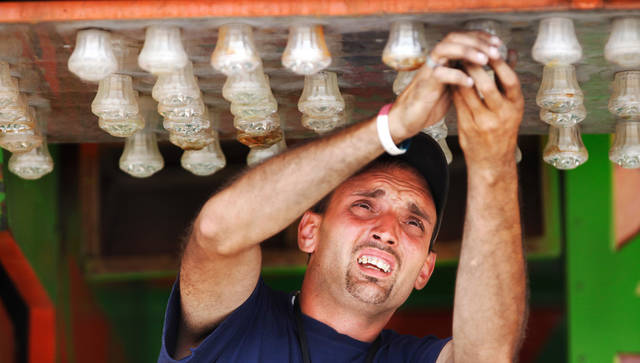 Matt Perry replaces the lenses on some of the lights on this midway attraction called the Cuckoo House. Midway and carnival workers  were busy most of Tuesday, Sep. 13, 2011, assembling game booths and rides, and washing and cleaning tarps, tents, seats  of the rides as they work to complete their tasks in time for the opening of the State Fair this Thursday at State Fair Park in Oklahoma City.   Photo by Jim Beckel, The Oklahoman