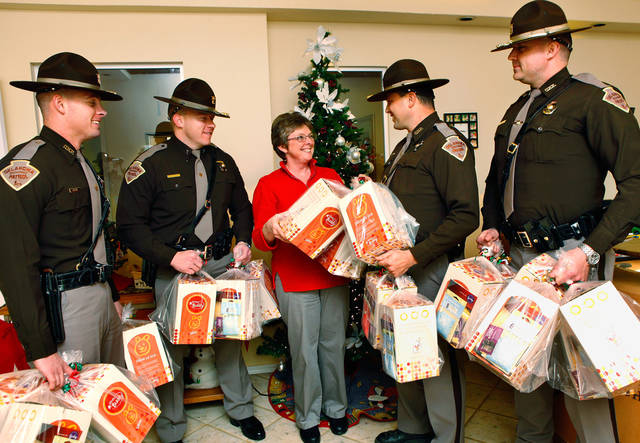 OKLAHOMA HIGHWAY PATROL / OHP / DONATED / DONATION: Oklahoma State Troopers donate to Ronald McDonald House in Oklahoma City, Wednesday, Dec. 21, 2011.  From left are Trooper B.J. Keelimg,  Lt. Scott Hampton, Darla Peterson, manager of the Ronald McDonald House, Trooper James Reinecker and Trooper Brad Dansby.  Photo by Jim Beckel, The Oklahoman