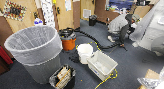 Buckets and wastebaskets collect water dripping from the ceiling as a cleanup worker vacuums up water from a soaked carpet in the principal's office at Monroe Elementary School in Oklahoma City Wednesday, Jan. 25, 2012. Rain water leaked through the ceiling as thunderstorms moved through the metro area overnight. Photo by Paul B. Southerland, The Oklahoman
