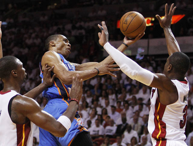 Oklahoma City Thunder point guard Russell Westbrook (0) shoots against Miami Heat power forward Chris Bosh (1) and shooting guard Dwyane Wade (3) during the second half at Game 3 of the NBA Finals basketball series, Sunday, June 17, 2012, in Miami. (AP Photo/Lynne Sladky) ORG XMIT: NBA148