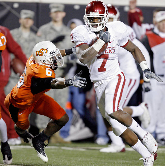 Oklahoma's DeMarco Murry (7) gets running room past Oklahoma State's Ricky Price (6) during the first half of the college football game between the University of Oklahoma Sooners (OU) and Oklahoma State University Cowboys (OSU) at Boone Pickens Stadium on Saturday, Nov. 29, 2008, in Stillwater, Okla. STAFF PHOTO BY CHRIS LANDSBERGER