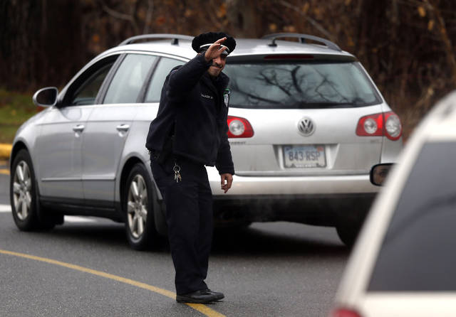 Easton police officer J. Sollazzo waves to a returning students as cars pull into Hawley School, Tuesday, Dec. 18, 2012, in Newtown, Conn.  Classes resume Tuesday for Newtown schools except those at Sandy Hook. Buses ferrying students to schools were festooned with large green and white ribbons on the front grills, the colors of Sandy Hook. At Newtown High School, students in sweatshirts and jackets, many wearing headphones, betrayed mixed emotions.  Adam Lanza walked into Sandy Hook Elementary School in Newtown,  Friday and opened fire, killing 26 people, including 20 children, before killing himself.(AP Photo/Jason DeCrow) ORG XMIT: CTJD112