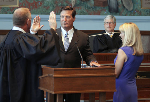 Oklahoma Supreme Court Justice Joseph M. Watt administers the oath of office to new District Judge Timothy R. Henderson as his wife Karen watches, during a swearing-in ceremony at the Oklahoma County Courthouse in Oklahoma City, OK, Monday, July 23, 2012,  By Paul Hellstern, The Oklahoman