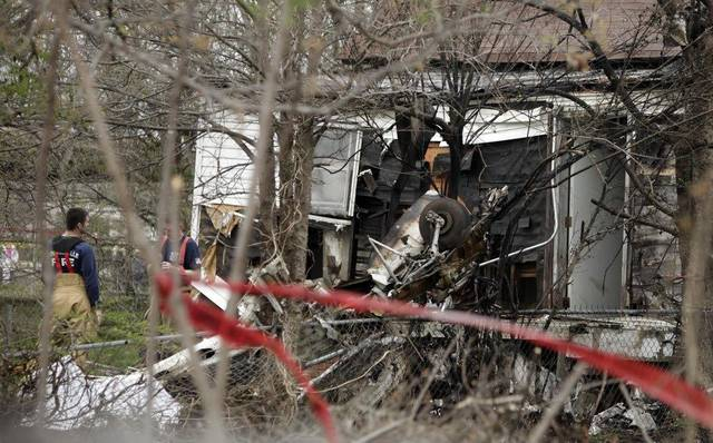 Parts of a small plane can be seen where it crashed into the back of a house in Collinsville on Sunday. Firefighters Photo BY Mike Simons, The Tulsa World