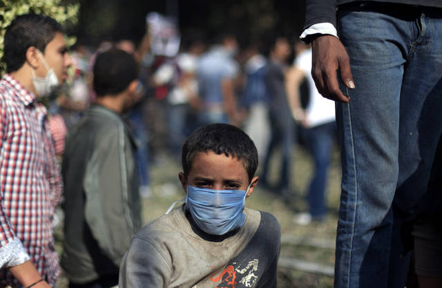 An Egyptian boy wears a mask during clashes security forces near Tahrir square, where an opposition rally has been called for to voice rejection of President Morsi's seizure of near absolute powers, in Cairo, Egypt, Tuesday, Nov. 27, 2012. Egyptian protesters and police clashed in Cairo on Tuesday just hours ahead of a planned massive rally by opponents of the country's Islamist president demanding he rescind decrees that granted him near-absolute powers.(AP Photo/ Khalil Hamra)