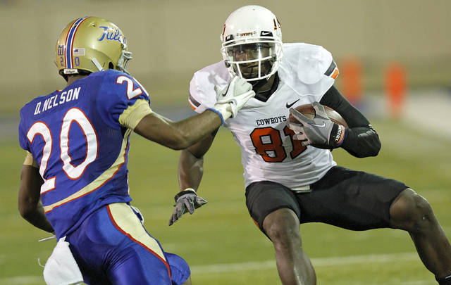 Oklahoma State's Justin Blackmon (81) tries to get more yards past Tulsa's Marco Nelson (20) during a college football game between the Oklahoma State University Cowboys and the University of Tulsa Golden Hurricane at H.A. Chapman Stadium in Tulsa, Okla., Sunday, Sept. 18, 2011. Photo by Chris Landsberger, The Oklahoman