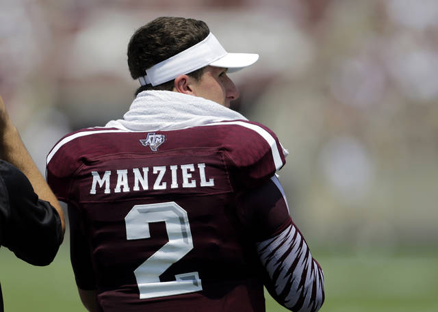 "Texas A&M's Johnny Manziel watches from the sidelines during the second quarter of an NCAA college football game against Rice, Saturday,  Aug. 31, 2013, in College Station, Texas.  Manziel has been suspended for the first half of the team's game for what the school said was an ""inadvertent"" violation of NCAA rules by signing autographs. (AP Photo/Eric Gay)"