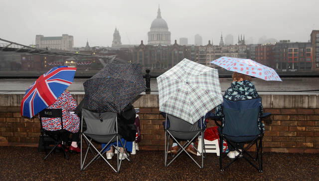 Royal revellers wait in the rain on the South Bank of the river Thames, London, several hours before the start of the Diamond Jubilee river pageant Sunday June 3, 2012. More than 1,000 boats were to sail down the Thames on Sunday in a flotilla tribute to Queen Elizabeth II's 60 years on the throne that organizers are calling the biggest gathering on the river for 350 years. Despite cool, drizzly weather, hundreds of thousands of people are expected to line the riverbanks in London, feting the British monarch whose longevity has given her the status of the nation's favorite grandmother. Seen at rear is St. Pauls cathedral.(AP Photo/ Lewis Whyld/PA) UNITED KINGDOM OUT NO SALES NO ARCHIVE